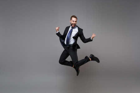Joyful young business man in classic black suit shirt tie posing isolated on grey background. Achievement career wealth business concept. Mock up copy space. Jumping, doing winner gesture, screaming.