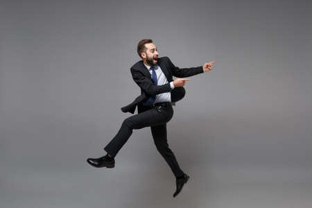 Side view of funny young business man in classic suit shirt tie posing isolated on grey background. Achievement career wealth business concept. Mock up copy space. Jumping, point index fingers aside.