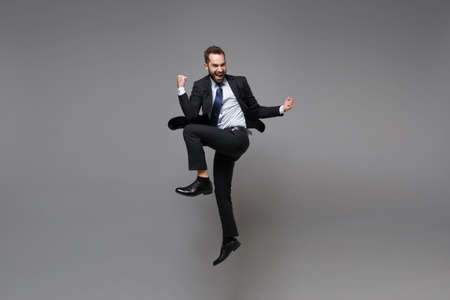 Overjoyed young business man in classic black suit shirt tie posing isolated on grey background. Achievement career wealth business concept. Mock up copy space. Jumping doing winner gesture screaming.