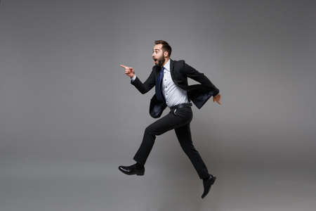 Side view of excited young business man in classic suit shirt tie posing isolated on grey background. Achievement career wealth business concept. Mock up copy space. Jumping, point index finger aside. Banco de Imagens