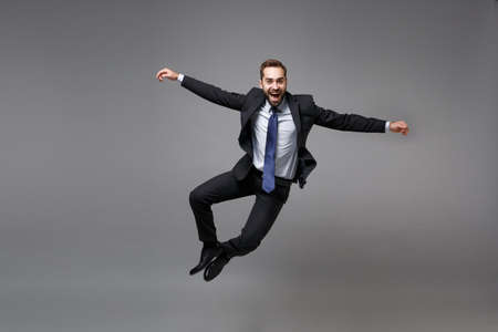 Cheerful young business man in classic black suit shirt tie posing isolated on grey background. Achievement career wealth business concept. Mock up copy space. Jumping, spreading hands, having fun.