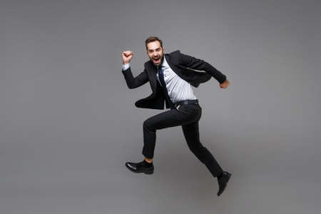 Side view of funny young business man in classic suit shirt tie posing isolated on grey background. Achievement career wealth business concept. Mock up copy space. Jumping, running, fooling around.