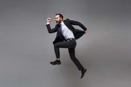 Side view of crazy young business man in classic suit shirt tie posing isolated on grey background. Achievement career wealth business concept. Mock up copy space. Jumping, running, fooling around.