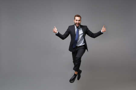 Excited young bearded business man in classic black suit shirt tie posing isolated on grey wall background. Achievement career wealth business concept. Mock up copy space. Jumping, showing thumbs up.