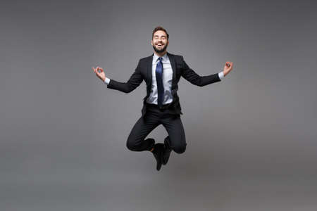 Smiling young business man in suit shirt tie posing isolated on grey background. Achievement career wealth business concept. Mock up copy space. Jumping hold hands in yoga gesture relaxing meditating. Banco de Imagens
