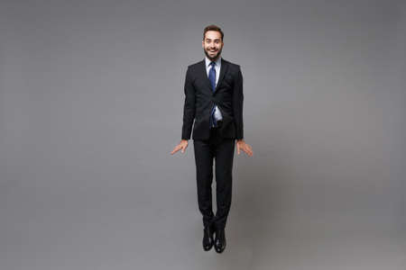 Smiling young business man in classic black suit shirt tie posing isolated on grey wall background. Achievement career wealth business concept. Mock up copy space. Jumping, fooling around, having fun.