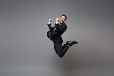 Happy young business man in classic black suit shirt tie posing isolated on grey background. Achievement career wealth business concept. Mock up copy space. Jumping, doing winner gesture, screaming. Banco de Imagens