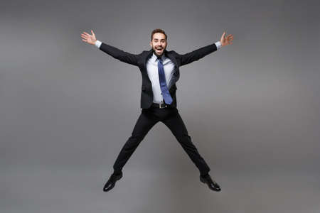 Cheerful young business man in black suit shirt tie posing isolated on grey background. Achievement career wealth business concept. Mock up copy space. Jumping, spreading hands and legs, having fun.