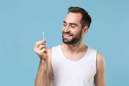 Bearded man 20s years old in white shirt hold cotton swab stick for ear cleaning isolated on blue pastel background studio portrait. Skin care healthcare cosmetic procedures concept Mock up copy space