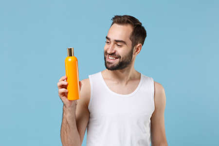 Bearded young man 20s years old in white shirt hold bottle of shampoo isolated on blue pastel wall background, studio portrait. Skin care healthcare cosmetic procedures concept. Mock up copy space.