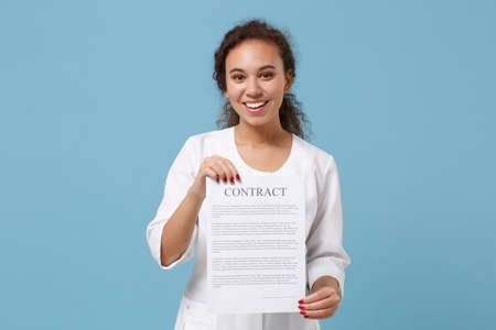 Smiling african american female doctor woman in white medical gown hold contract document isolated on blue background studio portrait. Healthcare personnel medicine health concept. Mock up copy space. Banco de Imagens