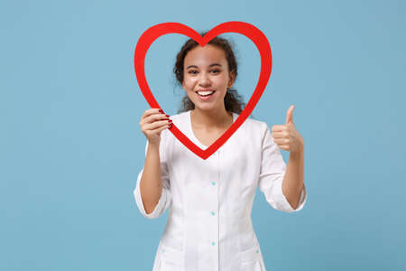African american doctor woman isolated on blue background. Female doctor in white medical gown hold red wooden heart showing thumb up. Healthcare personnel medicine health concept. Mock up copy space. Banque d'images