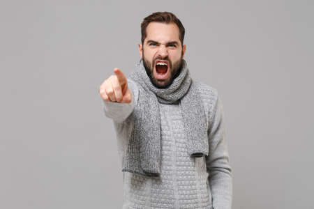 Angry young man in gray sweater scarf posing isolated on grey background in studio. Healthy fashion lifestyle, cold season concept. Mock up copy space. Point index finger on camera screaming swearing.