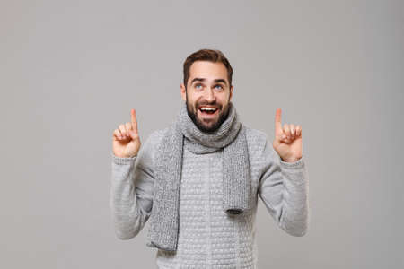 Funny young man in gray sweater, scarf posing isolated on grey background studio portrait. Healthy fashion lifestyle people emotions cold season concept. Mock up copy space. Pointing index fingers up.