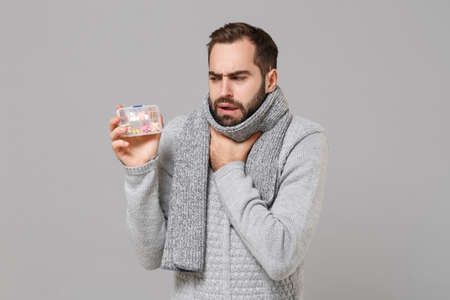 Young man in gray sweater, scarf isolated on grey background in studio. Healthy lifestyle, ill sick disease treatment, cold season concept. Mock up copy space. Hold daily pill box, put hand on throat.