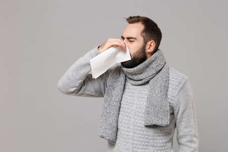 Young man in gray sweater, scarf isolated on grey wall background. Healthy lifestyle, ill sick disease treatment, cold season concept. Mock up copy space. Having runny nose, blowing nose to napkin. Stock Photo