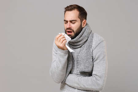 Young man in gray sweater, scarf isolated on grey background. Healthy lifestyle, ill sick disease treatment cold season concept. Mock up copy space. Coughing sneezing covering mouth with paper napkin.