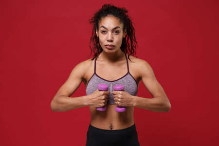 Strong young african american sports fitness woman in sportswear working out isolated on red wall background in studio. Sport exercises healthy lifestyle concept. Make exercise for arms with dumbbell.