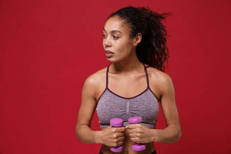Beautiful young african american sports fitness woman in sportswear work out isolated on red background. Sport exercises healthy lifestyle concept. Make exercise for arms with dumbbell, looking aside.