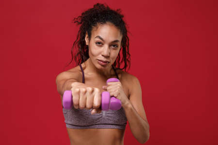Smiling young african american sports fitness woman in sportswear working out isolated on red background in studio. Sport exercises healthy lifestyle concept. Doing exercise for arms with dumbbell. Stockfoto