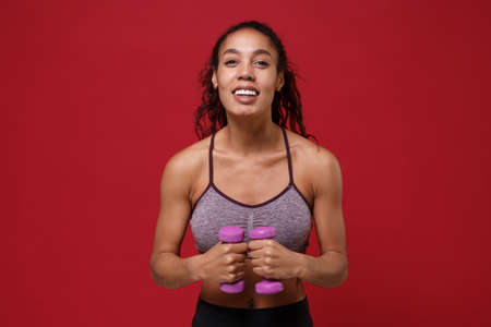 Cheerful young african american sports fitness woman in sportswear working out isolated on red background in studio. Sport exercises healthy lifestyle concept. Doing exercise for arms with dumbbell. Stockfoto