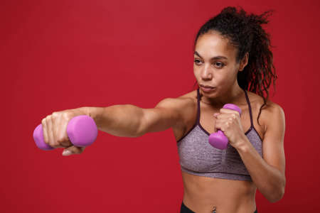 Confident young african american sports fitness woman in sportswear working out isolated on red background in studio. Sport exercises healthy lifestyle concept. Doing exercise for arms with dumbbell.
