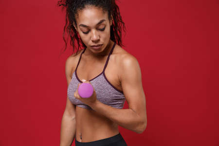 Beautiful young african american sports fitness woman in sportswear work out isolated on red background studio portrait. Sport exercises healthy lifestyle concept. Make exercise for arm with dumbbell.