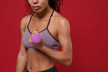 Cropped image of young african american sports fitness woman in sportswear work out isolated on red wall background. Sport exercises healthy lifestyle concept. Doing exercise for arms with dumbbell.