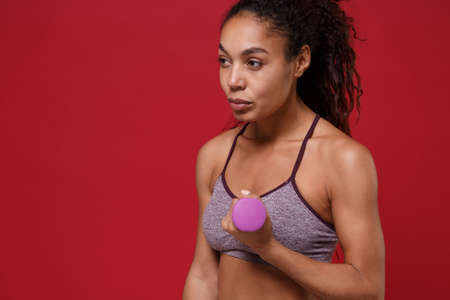 Strong young african american sports fitness woman in sportswear work out isolated on red background. Sport exercises healthy lifestyle concept. Make exercise for arms with dumbbell, looking aside. Stockfoto