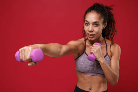 Attractive young african american sports fitness woman in sportswear working out isolated on red background in studio. Sport exercises healthy lifestyle concept. Doing exercise for arms with dumbbell. Stockfoto