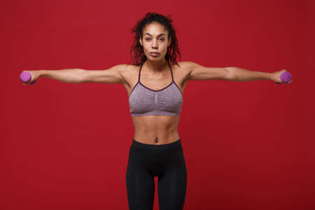 Strong young african american sports fitness woman in sportswear work out isolated on red background. Sport exercises healthy lifestyle concept. Spreading hands, doing exercise for arms with dumbbell.