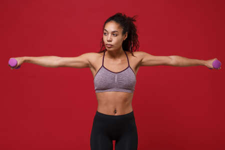 Beautiful young african american sports fitness woman in sportswear work out isolated on red background. Sport exercises healthy lifestyle concept. Spreading hands make exercise for arm with dumbbell.
