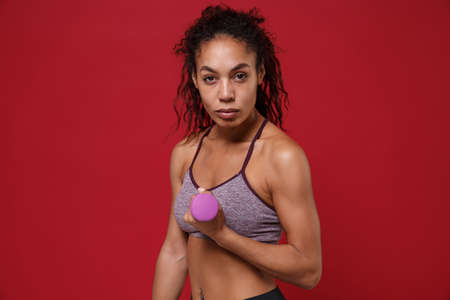 Confident young african american sports fitness woman in sportswear work out isolated on red background studio portrait. Sport exercises healthy lifestyle concept. Make exercise for arm with dumbbell.
