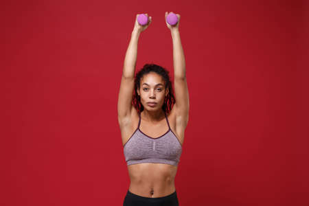 Strong young african american sports fitness woman in sportswear working out isolated on red background. Sport exercises healthy lifestyle concept. Rising hands, doing exercise for arms with dumbbell.