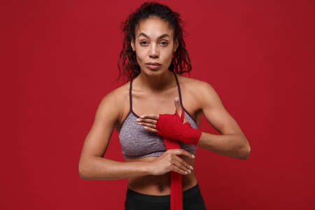 Confident young african american sports fitness woman in sportswear posing working out isolated on red background. Sport exercises healthy lifestyle concept. Reeling up sports bandages on her hands.