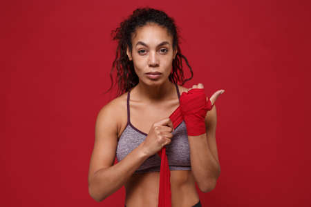 Strong young african american sports fitness woman in sportswear posing working out isolated on red wall background. Sport exercises healthy lifestyle concept. Reeling up sports bandages on her hands.