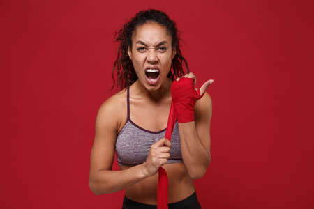Crazy african american sports fitness woman in sportswear posing working out isolated on red background. Sport exercises healthy lifestyle concept. Reeling up sports bandages on her hands, screaming.