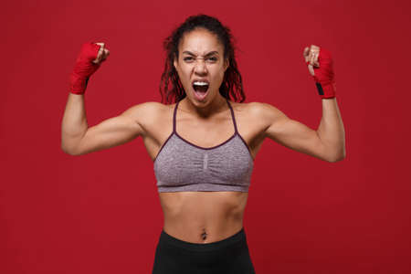 Crazy african american fitness boxer woman in sportswear working out isolated on red background. Sport exercises healthy lifestyle concept. Wearing sports bandages on hands, showing biceps, screaming.