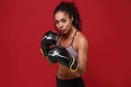 Beautiful young african american sports fitness boxer woman in sportswear working out isolated on red wall background. Sport exercise healthy lifestyle concept. Make boxing exercises in boxing gloves.