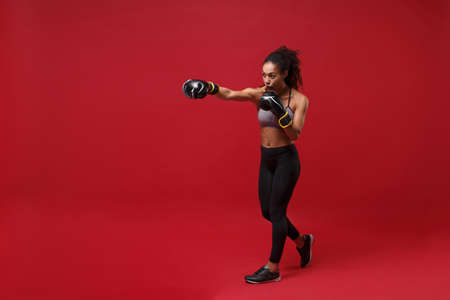 Strong young african american sports fitness boxer woman in sportswear working out isolated on red wall background. Sport exercise healthy lifestyle concept. Doing boxing exercises in boxing gloves.