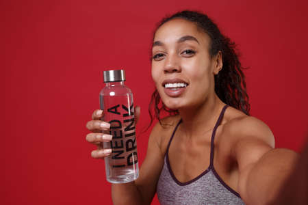 Close up of african american sports fitness woman in sportswear posing working out isolated on red background. Sport exercises healthy concept. Doing selfie shot on mobile phone, hold water bottle.
