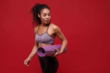 Beautiful young african american sports fitness woman in sportswear working out isolated on red background studio portrait. Sport exercises healthy lifestyle concept. Hold fitness mat, looking aside.
