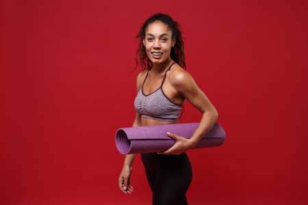 Cheerful young african american sports fitness woman in sportswear working out isolated on red background studio portrait. Sport exercises healthy lifestyle concept. Hold fitness mat, looking camera.