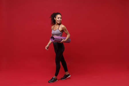Smiling young african american sports fitness woman in sportswear working out isolated on red background studio portrait. Sport exercises healthy lifestyle concept. Hold fitness mat, looking aside.