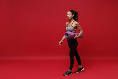 Attractive young african american sports fitness woman in sportswear working out isolated on red background studio portrait. Sport exercises healthy lifestyle concept. Hold fitness mat, looking aside.