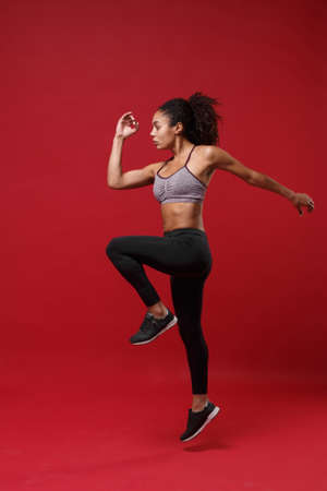 Side view of young african american fitness woman in sportswear posing working out isolated on red wall background studio portrait. Sport exercises healthy lifestyle concept. Jumping like running.