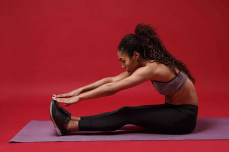 Side view of young african american woman in sportswear posing working out isolated on red background. Sport exercises healthy lifestyle concept. Sitting on fitness mat, doing stretching exercising.