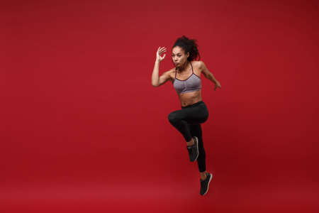 Attractive young african american fitness woman in sportswear posing working out isolated on red wall background, studio portrait. Sport exercises healthy lifestyle concept. Jumping like running. Reklamní fotografie