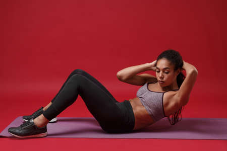 Side view of young african american woman in sportswear posing working out isolated on red background. Sport exercises healthy lifestyle concept. Sitting on fitness mat, doing abdominal exercises.