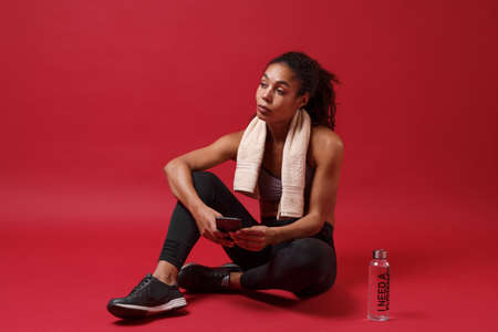 Beautiful young african american woman in sportswear working out isolated on red background. Sport exercises healthy lifestyle concept. Sit with towel over her neck, water bottle, using mobile phone. Reklamní fotografie